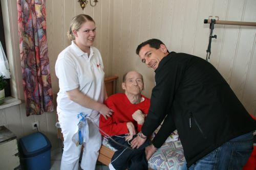 Foto: Vl. DRK-Schwester Christine Renard der Sozialstation Siegen erhält Hilfe von Jens Kamieth, um den Patienten Dieter Jäckel nach seiner Grund- und Behandlungspflege in seinen Spezialrollstuhl zu setzen