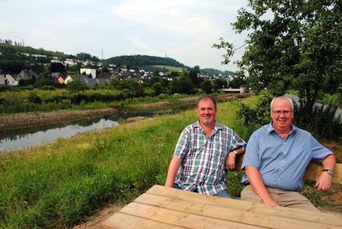 """""""Logenplatz"""" an der naturnah umgestalteten Ruhr: Umweltingenieur Friedhelm Koch (li.) und Bürgermeister Ralf Péus """"testen"""" die neue Sitzgruppe. Foto: Gemeinde Bestwig"""