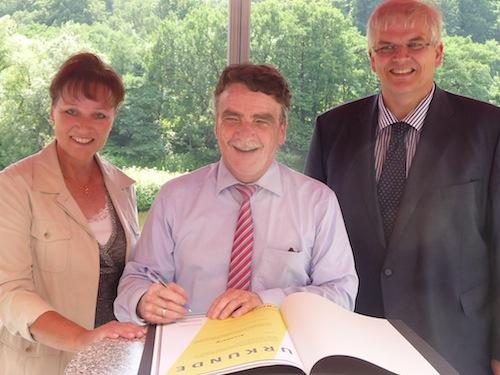 Der NRW-Verkehrsminister unterzeichnet im Beisein von Christine Fuchs, Geschäftsführerin der AGFS, und Bürgermeister Hans-Josef Vogel die Urkunde, mit der Arnsberg in die AGFS aufgenommen wird. (Quelle: Stadt Arnsberg)