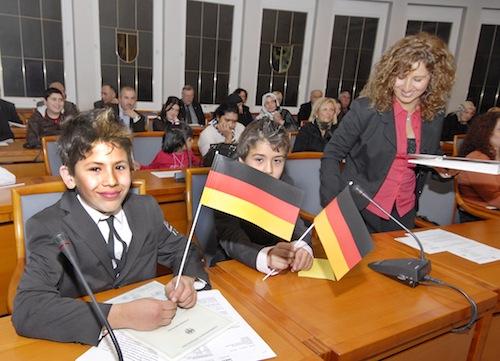 """Zum ersten Mal veranstaltete der Kreis Soest am 1. Dezember 2009 eine Einbürgerungsfeier. Diese beiden jungen Neubürger zeigten sofort """"Flagge"""", als sie die Urkunde erhalten hatten (Foto: Wilhelm Müschenborn/Kreis Soest)."""
