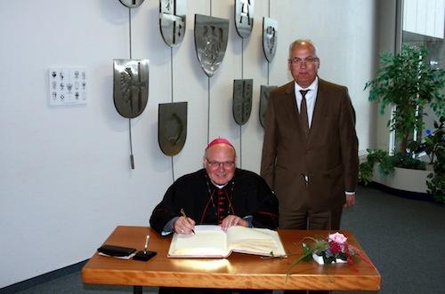 Photo of Weihbischof trägt sich ins Goldene Buch ein