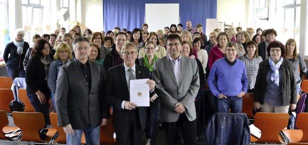 Bürgermeister Dr. Peter Paul Ahrens (M.) präsentiert gemeinsam mit allen Beteiligten die Kooperationsvereinbarung zum Übergang von der Kita zur Grundschule (Foto: Stadt Iserlohn).
