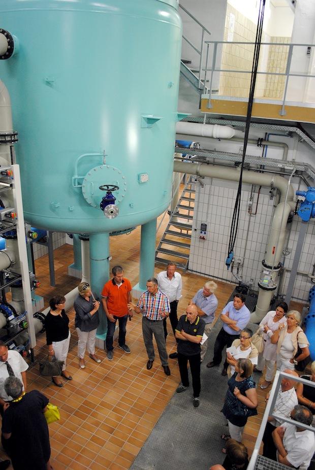 Robert Dietrich, Technischer Geschäftsführer des HSW, erläutert den Besuchern vom Lions-Club Ols-berg-Bestwig, die verschiedenen Schritte der Trinkwasseraufbereitung. Im Hintergrund: Ein rund sie-ben Meter hoher Filterkessel der Aktivkohlefiltration (Foto: Hochsauerlandwasser GmbH).