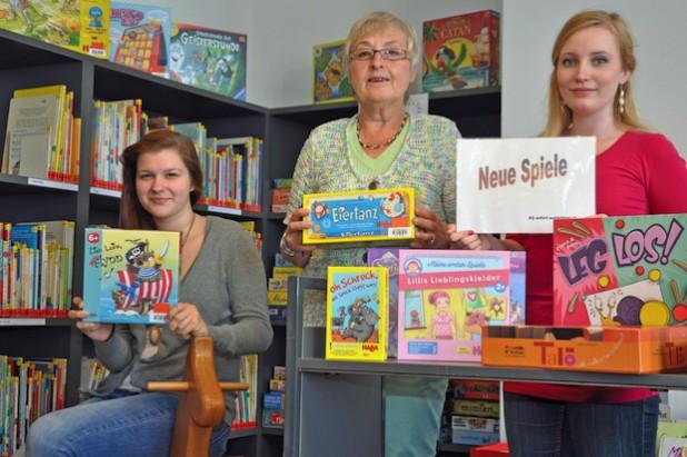 Die Mitarbeiterinnen der Stadtbücherei (v.l.), Ricarda Grieß, Barbara Bürger und Darja Lerch, präsentieren einen Teil der neuen Spieleauswahl (Foto: Stadt Lippstadt).