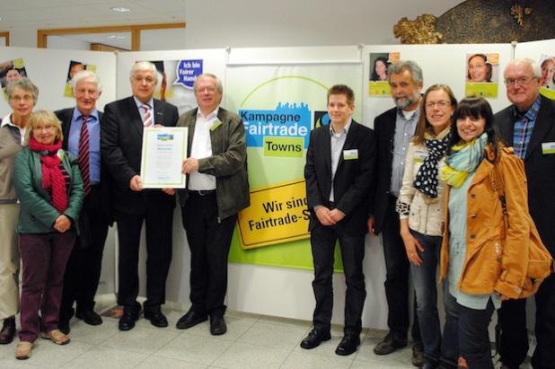 Aus der Hand von Fairtrade-Ehrenbotschafter Manfred Holz (3. v.l.) erhielten Bürgermeister Uli Hess und die Mitglieder der Steuerungsgruppe das Fairtrade-Siegel (Foto: Stadt Meschede).