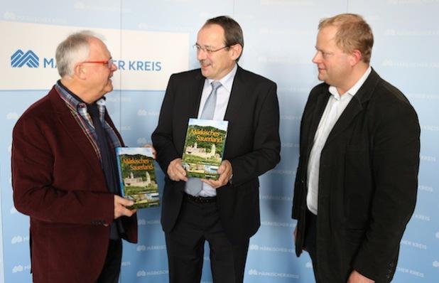 Autor Joachim Nierhoff (links) überreicht Landrat Thomas Gemke seinen neuen Bildband. Rechts Markus Holzhauer vom Sutton Verlag (Foto: Hendrik Klein/Märkischer Kreis).