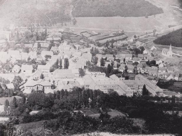 """Das Foto wurde um das Jahr 1872 aufgenommen. Man schaut auf Niedermarsberg. Im Vordergrund sind die Gebäude der Westfälischen Klinik in doppelter """"H-Form"""" zu sehen. Hinter dem linken """"H"""" wird gerade die Anstaltskirche auf der ehemaligen Bleichwiese erbaut. Sie wurde aus dem Steinmaterial des Chores der alten Klosterkirche erstellt (Quelle: Marsberger Geschichten - Schlüssel zur Vergangenheit e.V.)."""