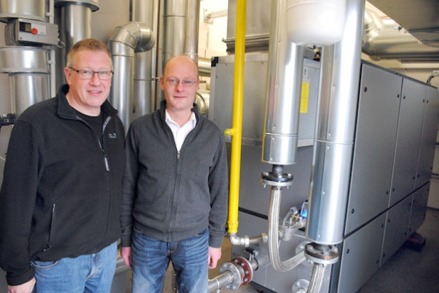 Geschäftsführer Andreas Rüther (l.) und Badleiter Johannes Butterweck präsentieren das neue Blockheizkraftwerk in der Heizzentrale des AquaOlsberg (Foto: Stadt Olsberg).