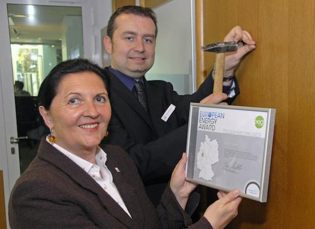 Landrätin Eva Irrgang und Klimaschutzmanager Frank Hockelmann brachten im Kreishaus-Foyer die Urkunde an, mit der die Teilnahme am European Energy Award bescheinigt wird (Foto: Wilhelm Müschenborn/Kreis Soest).