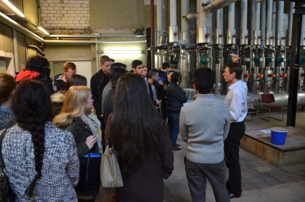 Prof. Gerald Lange erkundet mit den Erstsemestern des Studiengangs Wirtschaftsingenieurwesen-Gebäudesystemtechnolgie die Heizzentrale im Untergeschoss des Hochschulgebäudes an der Haldener Straße (Foto: Fachhochschule Südwestfalen).