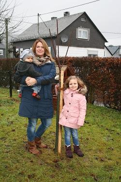 Frisch gepflanzt! Das Süßkirschenbäumchen für den kleinen Felix wird nun in Altenseelbach Wurzeln schlagen. Das freut auch Verena und Stella Meyer (Foto: Gemeinde Neunkirchen).