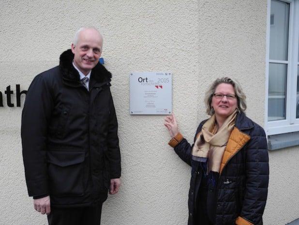 """An der Rathauswand hängt die Plakette """"Ort des Fortschritts"""", die Bürgermeister Christoph Ewers und NRW-Wissenschaftsministerin Svenja Schulze enthüllten (Foto: Gemeinde Burbach)."""