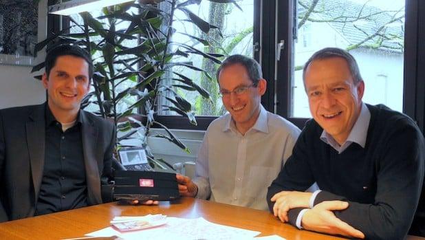 Bürgermeister Christian Pospischil (l.) nahm aus den Händen von Thomas Corte (r.) und Christian Springob von der Werbegemeinschaft Attendorn symbolisch einen ersten Freifunk-Router entgegen (Foto: Hansestadt Attendorn).