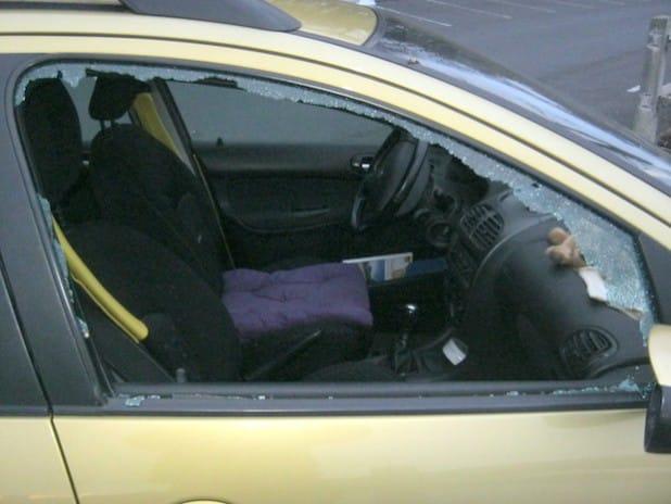 Eingeschlagene Seitenscheibe an dem Peugeot (Foto: Kreispolizeibehörde Soest)