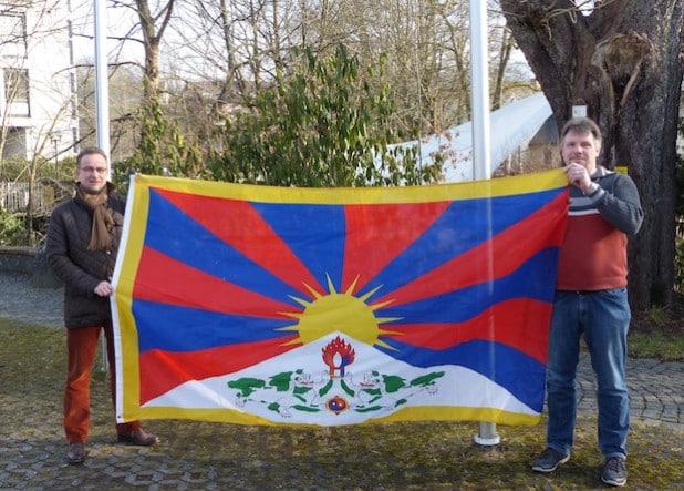 Bürgermeister Hans-Peter Hasenstab und sein Mitarbeiter Karsten Valenta präsentieren vor dem Hissen die Flagge Tibets am Marktplatz (Foto: Stadt Hilchenbach).