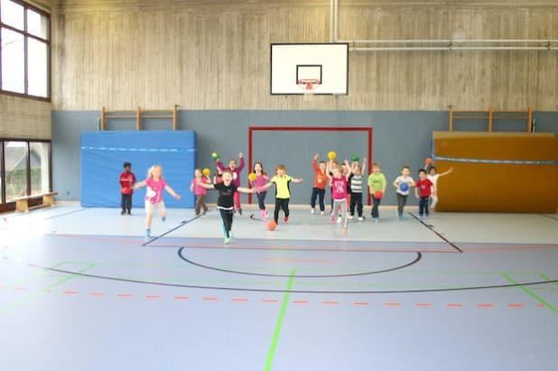 Die Erstklässler toben vergnügt über den frisch renovierten Hallenboden der Sporthalle der Mariengrundschule (Foto: Stadt Meschede).