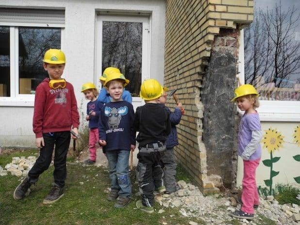 Mit Hammer und Schutzausrüstung legten die Kinder des Kindergartens Würgendorf schon los und läuteten den Abbruch des Gebäudes ein (Foto: Gemeinde Burbach).