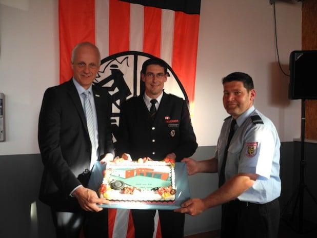 Am Freitag wurde in Lippe das neue Feuerwehrgerätehaus eingeweiht. Anstatt eines Schlüssels überreichte Bürgermeister Christoph Ewers einen Kuchen an Wehrführer Tobias Klein (mi.) und Lippes Löschzugführer Jens Wildfeuer (re.) - Foto: Gemeinde Burbach.