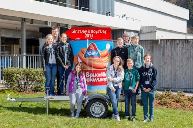 """Die Teilnehmerinnen und Teilnehmer des Girls' Day und Boys' Day 2015 mit der Personalleiterin Petra Palla sowie dem bekanntesten Produkt der Firma Metten, die """"Dicke Sauerländer"""" Bockwurst (Foto: Metten Fleischwaren GmbH & Co. KG)."""