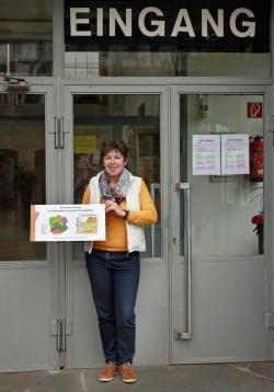 Empfangsdame Ursula Albers mit dem neuen Schild als Einrichtung des nationalen Geopark GrenzWelten (Foto: Bergbaumuseum Ramsbeck GmbH)