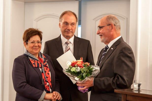 Elmar Reuter (Mitte) mit seiner Ehefrau (rechts) und Regierungspräsident Dr. Gerd Bollermann (Foto: Bezirksregierung Arnsberg).