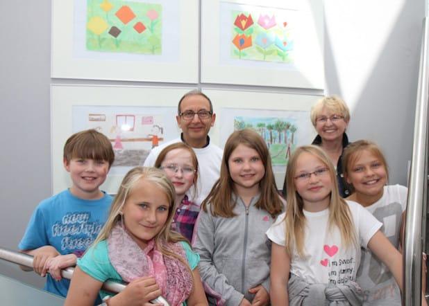 Francesco Fazio (Allgemeinmediziner) und Ingrid Dlugai (Leiterin der Kunst-AG) freuen sich gemeinsam mit den Kindern der Georgschule über die willkommenen Hingucker im RIGA-RING-Ärztehaus (Foto: RIGA-RING).