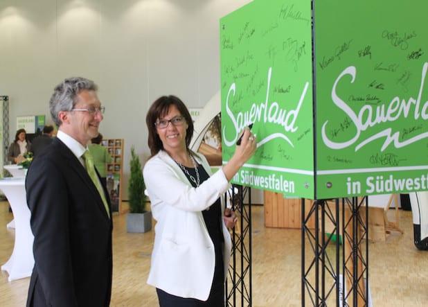 Das angepasste Sauerland-Logo ist ein Ergebnis des Sauerland-Tages: Prof. Dr. Susanne Leder, Fachhochschule Südwestfalen, und Thomas Weber, Geschäftsführer Sauerland-Tourismus, setzten mit ihren Unterschriften ein Zeichen für das einheitliche Bild der Region (Foto: Sauerland-Tourismus e.V./Nadja Reh).