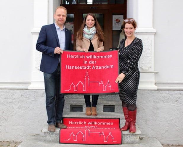 Ronja Wockel von der Hansestadt Attendorn (Bildmitte) überbrachte die ersten Fußmatten an die Attendorner Einzelhändler Nicole Kost (rechts) und Michael Frey (Foto: Hansestadt Attendorn).