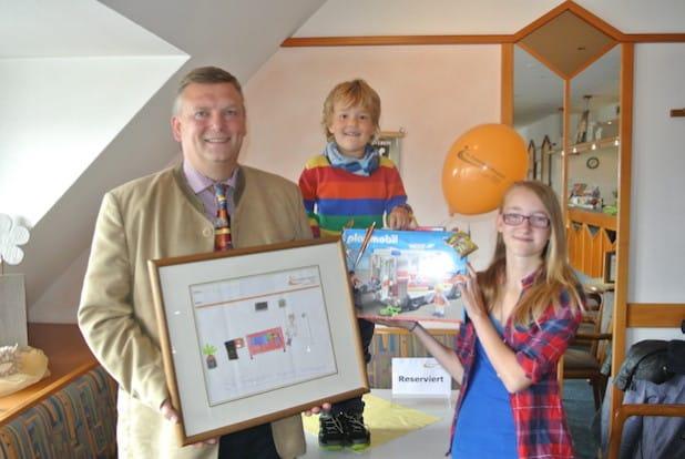 Von links: Geschäftsführer Christian Jostes zeigt das Gewinnerbild. Leon und Marie freuen sich über ihren Preis (Foto: St. Franziskus-Hospital gGmbH).
