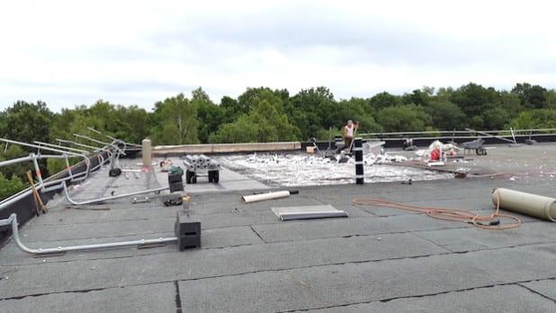 Ein Arbeitsplatz in luftigen Höhen. Bevor das Dach saniert und gedämmt werden kann, müssen die alten Baustoffe beseitigt werden (Foto: Gemeinde Neunkirchen).