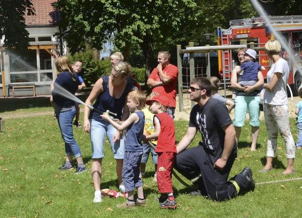 Begeistert löschen die Zwergenlandkinder unter Anleitung von Micha Kleinschmidt und Martin Aßhauer mit dem Feuerwehrstrahlrohr einen fiktiven Brand (Foto: Thomas Weinstock/Kreis Soest).
