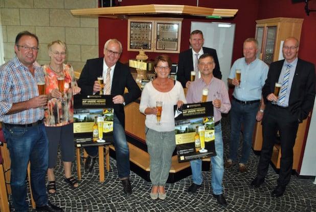 """""""Auf unsere Heimat"""": Bestwigs Bürgermeister Ralf Péus (3.v.li.) und Manfred Nieder (4.v.re.), Gebietsverkaufsleiter der Warsteiner Brauerei, stellten mit den Ortsvorstehern (v.li.) Ulrich Bathen (Heringhausen), Adelheid Bamfaste (Velmede-Bestwig), Ulrike Mikitta (Andreasberg), Paul Schüttler (Ramsbeck), Manfred Ramspott (Ostwig) und Markus Sommer (Nuttlar) die Aktion vor (Foto: Gemeinde Bestwig)."""
