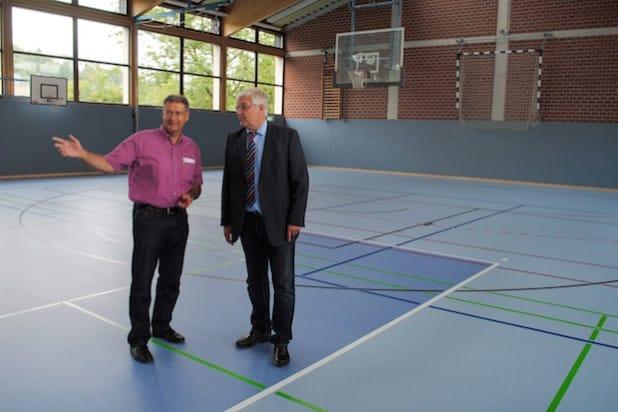 Dipl.-Ing. Peter Temmhoff (li.) stellt Bürgermeister Uli Hess den neuen Sportboden der Turnhalle am Rautenschemm vor. Bildnachweis: Stadt Meschede