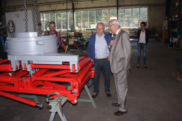 Landrat Dr. Karl Schneider (r.) wird von Geschäftsführer Josef Hanses (M.) durch die Fertigungshalle geführt (Foto: Pressestelle HSK).