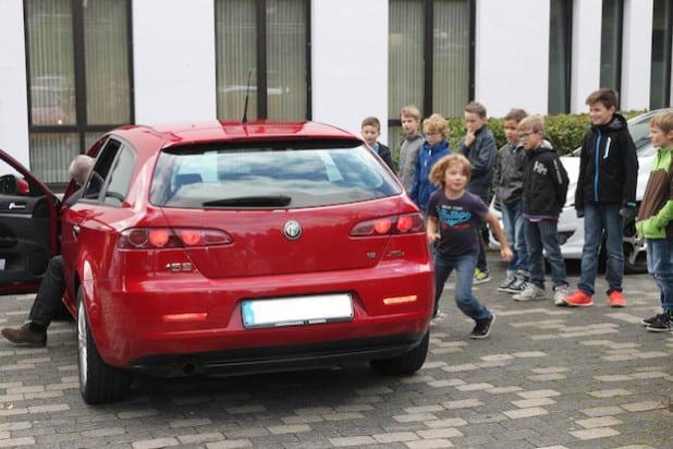 """Das Foto zeigt die Jungen beim Rollenspiel mit dem Trainer Wolfgang Selter, der ihnen die Gefahren des Themas """"Rund um's Fahrzeug"""" erklärt (Foto: Gemeinde Finnentrop)."""