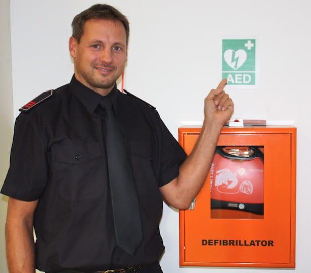 Jan Falke an einem Defibrillator im Olper Kreishaus. Das AED-Piktogramm weist häufig den Weg (Foto: Kreis Olpe).