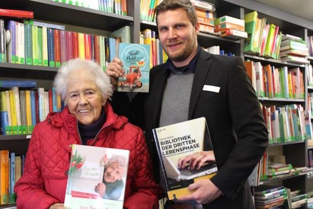 Leserin Maria Hüffer aus Rüthen und Nils Bald, Leiter der Fahrbücherei des Kreises Soest, freuen sich über das neue Bücherangebot für Seniorinnen und Senioren (Foto: Sebastian Gust/Kreis Soest).