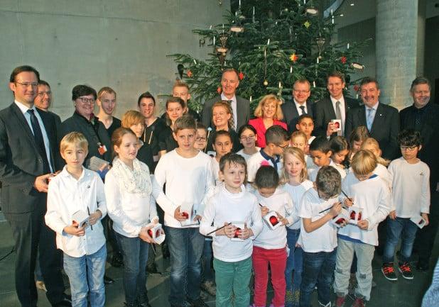 Die MJO-Musiker mit den Siegener Schülern und die Offiziellen vor dem neuen Weihnachtsbaum (Foto: Detlef Krüger/Märkischer Kreis).