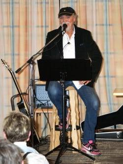 Hänsch liest und musiziert auf der Bühne - Foto: Klaus Peters