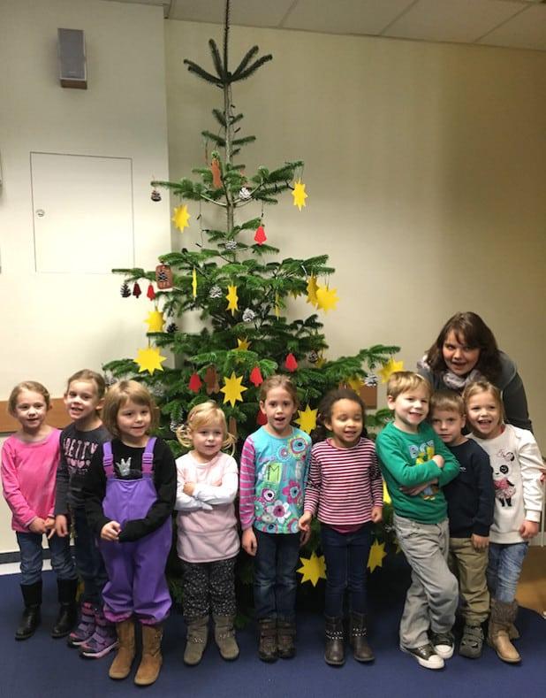 Stolz präsentieren die Kinder des Familienzentrums Werl-Nord mit ihrer Erzieherin Meike Laugsch den geschmückten Tannenbaum im Jobcenter Arbeit Hellweg Aktiv (AHA) - Foto: AHA.