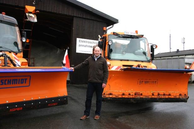 Marc Böhm, Leiter des Integrierten Baubetriebshofes, mit zwei der großen Räumfahrzeuge auf dem Gelände in Enste. Das Salzlager im Hintergrund ist bis zum Rand gefüllt. Nur der Winter fehlt (Foto: Stadt Meschede).