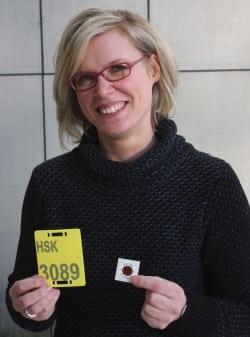 Melanie Mönig von der Unteren Landschaftsbehörde des HSK stellt das gelbe Reitkennzeichen und die neue braune Plakette für 2016 vor (Foto: Pressestelle HSK).