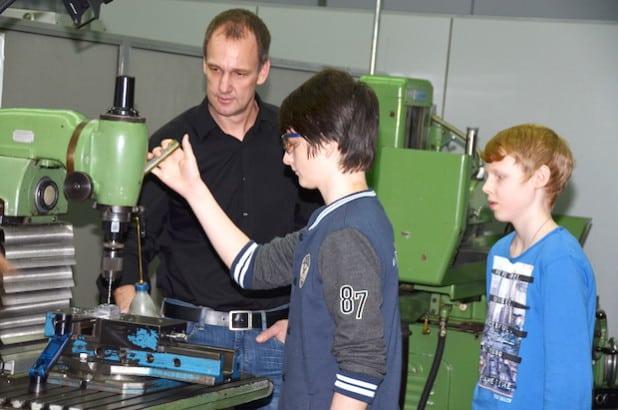 Berufsfelderkundung in der Firma Lumberg Connect GmbH, Martin Eilbrecht zeigt Marvin den richtigen Umgang mit einer Bohr-Fräsmaschine (Foto: Herget/Märkischer Kreis).