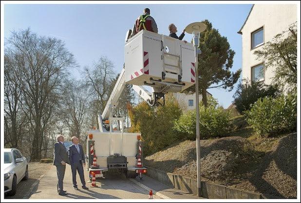 Heino Lange (links), Bürgermeister Dieter Dzewas und STL-Werkausschussvorsitzender Bernd Schildknecht (auf dem Steiger) machen sich vor Ort ein Bild vom Austausch der Leuchtmittel. Quelle: Stadt Lüdenscheid
