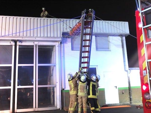 Mit Hilfe eines sogenannten Leiterhebels wird ein Mitarbeiter patientenorientiert vom Dach der Werkstatt gerettet. Foto: Dieter Dreier (Feuerwehr Lippstadt)