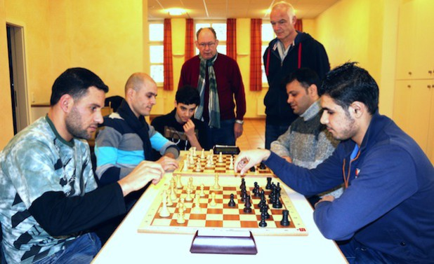 Integration mit dem Spiel der Könige: Über das Schachspiel haben sich Werner Weber, Wolfgang Petri (hinten) die al Doukhi Familie und Yamen el Medyeb (hinten rechts) kennengelernt. Quelle: Gemeinde Neunkirchen