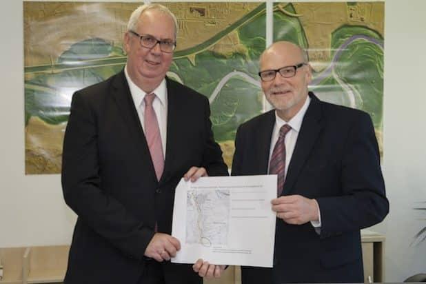 Bürgermeister Ralf Péus (links) nimmt den Förderbescheid von Abteilungsleiter Bernd Müller entgegen. Quelle: Bezirksregierung Arnsberg
