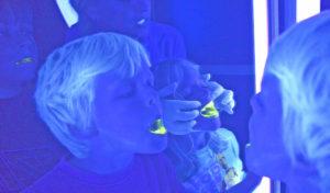 Kinder entdecken Karius und Baktus im Neonlicht