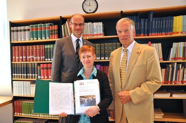 Bürgermeister Christof Sommer (l.) und Dr. Claudia Becker (m.) freuen sich über die Übergabe der Dokumentation aus 25 Jahren deutsch-russischer Partnerschaft zwischen Lippstadt und Krasnojarsk durch Herman Strutz (r.). Foto: Stadt Lippstadt
